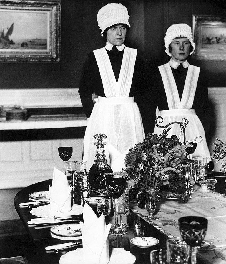 Sirvienta y sirvienta segunda preparadas para servir la cena - Bill Brandt